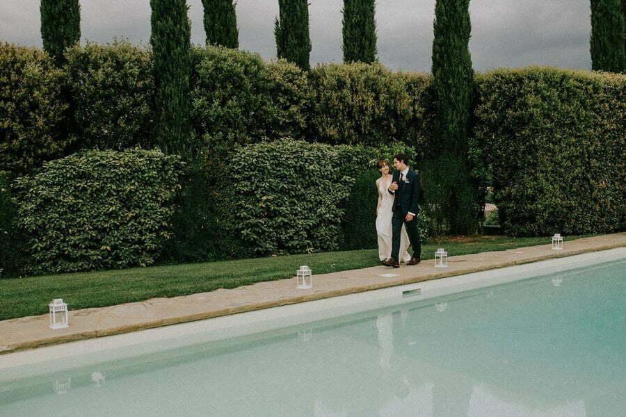 bride and groom walking near the pool